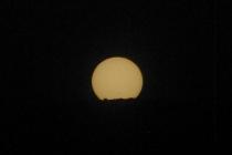 Puesta del sol con los árboles en el horizonte. Las manchas solares son visibles arriba de ellos.